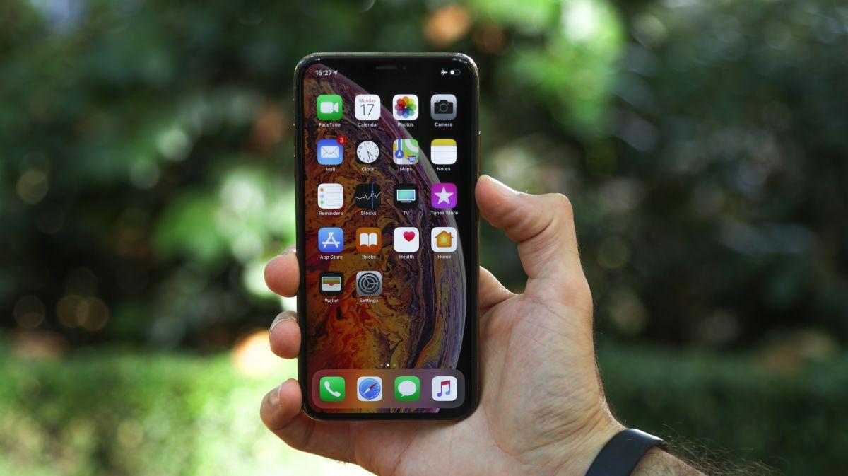 iPhone Xs sujetado por una mano de hombre mostrando su pantalla sin bordes