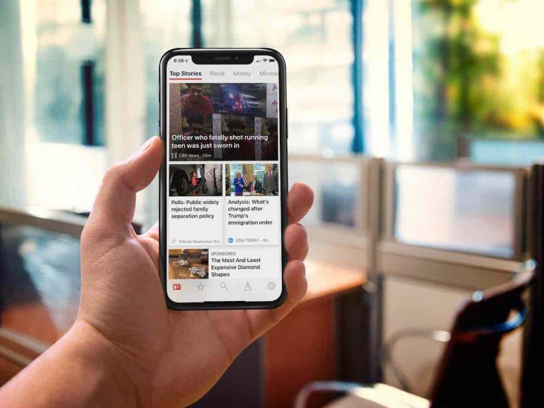 Teléfono celular tomado con una mano en donde se muestra la sección de Microsoft sobre noticias