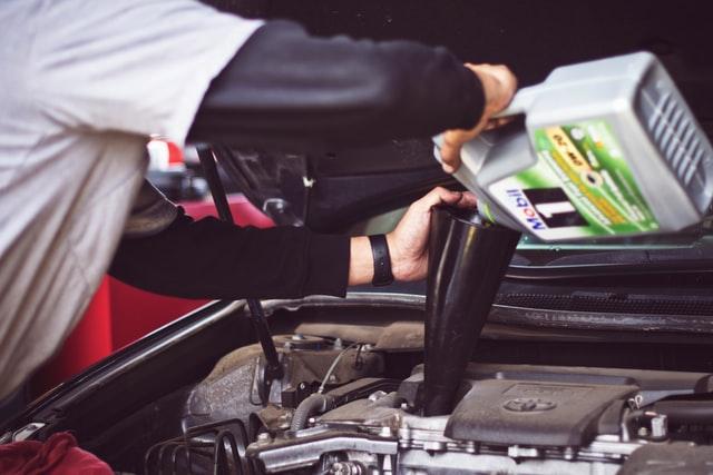 Hombre poniendo aceite a un auto